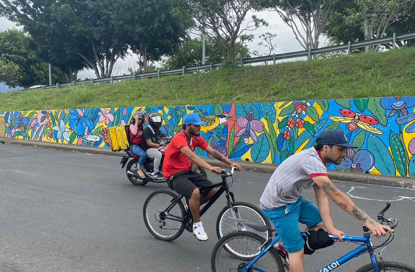 people crossing in front of rylyuk mural
