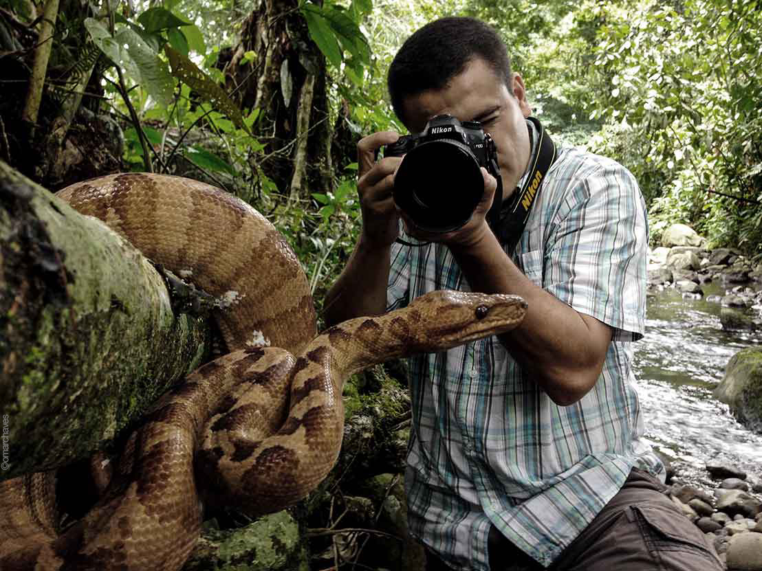 Photographer-Omar-Chaves-shooting-his-camera-next-to-a-large-boa